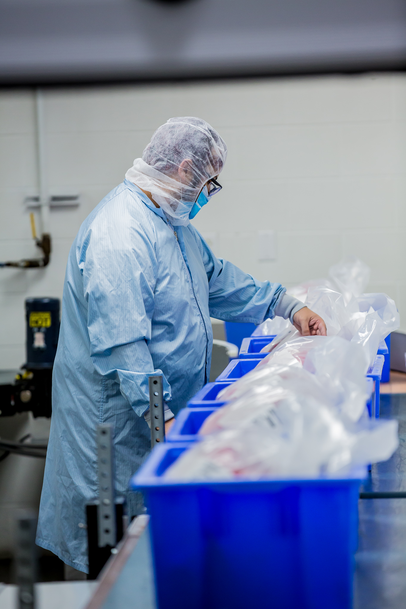 Person in clean room gear inspecting bags