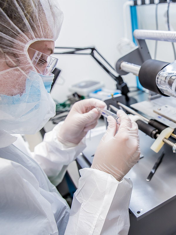 Woman wearing clean room gear while working and inspecting a medical object