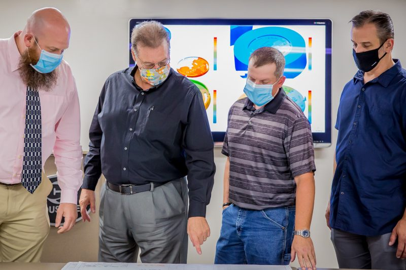 Four men wearing face masks talking and pointing