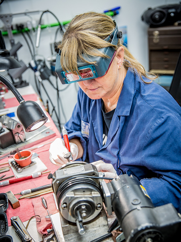 Woman wearing magnifying glasses to work on machine